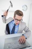 拿着在膝上型计算机的恼怒的商人锤子 库存照片