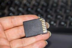 拿着在膝上型计算机背景的手SD卡片 图库摄影