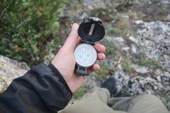 拿着在自然的旅客一个指南针 长圆规概念轻位于的映射定位开放下面 免版税库存图片
