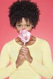 拿着在色的背景的一名非裔美国人的妇女的画象糖果 库存照片