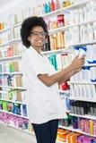 拿着在药房的女性化学家香波瓶 免版税库存图片