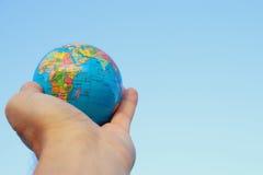 拿着在蓝天前面的男性手小地球 免版税库存照片