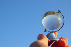 拿着在蓝天前面的男性手小水晶地球 库存图片