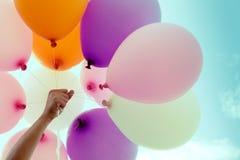 拿着在蓝天背景的妇女手五颜六色的气球 免版税库存照片