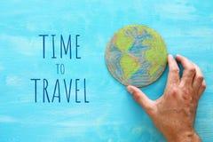 拿着在蓝色木背景的人手的顶视图图象地球地球 免版税库存照片
