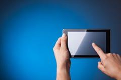 拿着在蓝色的手片剂个人计算机 免版税库存照片