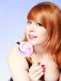 拿着在蓝色的Redhair女孩甜食物棒棒糖糖果 库存图片