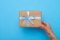 拿着在蓝色背景的女性的手一个礼物盒 免版税库存图片