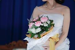 拿着在蓝色背景的新娘美丽的婚礼花束 图库摄影