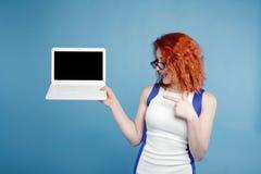 拿着在蓝色背景的美丽的红发女孩膝上型计算机孤立 安置文本 图库摄影