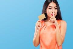 拿着在蓝色背景的购物的愉快的亚裔妇女销售卡片黑星期五假日 复制空间待售 免版税库存图片