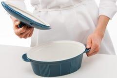 拿着在蓝色陶瓷平底锅上的女性厨师盒盖 库存照片