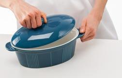 拿着在蓝色陶瓷平底锅上的女性厨师盒盖 库存图片