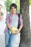 拿着在街道上的年轻人书 免版税库存照片