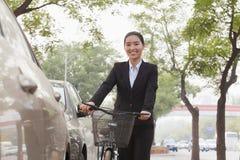 拿着在街道上的年轻微笑的女实业家一辆自行车,看照相机 免版税库存图片