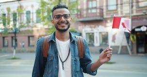 拿着在街道微笑的可爱的Abarian人画象加拿大旗子 股票视频