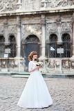 拿着在街道的微笑的新娘的全长侧视图婚礼花束 库存照片