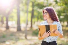 拿着在被弄脏的背景的微笑的学生女孩一本书 概念剪切在老纸读取眼镜表面上写字染黄 复制空间 库存照片