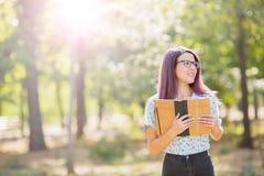 拿着在被弄脏的背景的微笑的学生女孩一本书 概念剪切在老纸读取眼镜表面上写字染黄 复制空间 库存图片