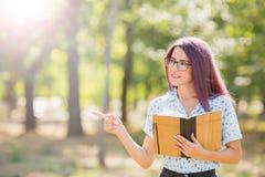 拿着在被弄脏的背景的微笑的学生女孩一本书 概念剪切在老纸读取眼镜表面上写字染黄 复制空间 免版税库存图片