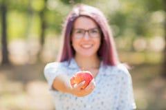 拿着在被弄脏的背景的愉快的逗人喜爱的女孩一个红色苹果 概念健康快餐 复制空间 库存图片