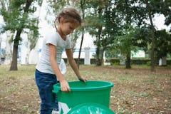 拿着在被弄脏的自然本底的一个逗人喜爱的小女孩一个大绿色回收站 生态污染概念 免版税库存图片