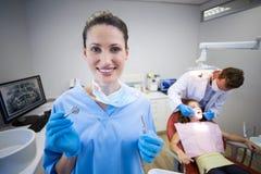 拿着在诊所的护士画象牙齿工具 免版税库存照片