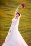 拿着在象草的领域的愉快的新娘侧视图画象花花束 库存照片
