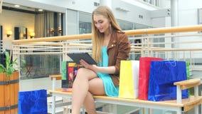 拿着在长凳的购物妇女数字式片剂 股票录像