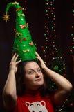 拿着在闪烁光背景的女孩一棵圣诞树  免版税图库摄影