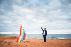 拿着在阴暗海和天空背景的英俊的小男孩飞行风筝 免版税库存照片