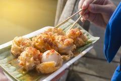 拿着在面团的微型油煎的淡菜,浮动市场 免版税库存照片