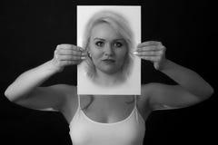 拿着在面孔前面的少妇一张纸 库存照片