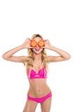 拿着在面孔前面的桃红色比基尼泳装的愉快的白肤金发的妇女桔子 图库摄影