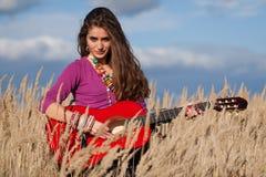 拿着在领域的国家女孩一把吉他反对蓝色多云天空背景 免版税库存图片
