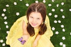 拿着在领域的小女孩一只蝴蝶有很多花 库存图片