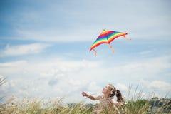 拿着在领域的愉快的微笑的小女孩飞行风筝在蓝色多云天空背景 免版税库存图片