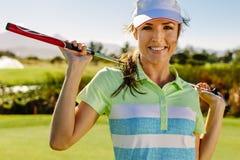 拿着在领域的美丽的女性高尔夫球运动员高尔夫俱乐部 免版税库存照片