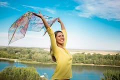 拿着在风的华美的少妇一条围巾在公园 库存图片