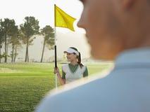 拿着在高尔夫球场的女性高尔夫球运动员旗子 库存图片