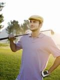 拿着在高尔夫球场的男性高尔夫球运动员俱乐部 免版税库存照片