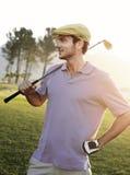 拿着在高尔夫球场的男性高尔夫球运动员俱乐部 库存图片