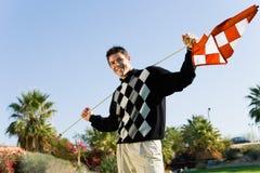 拿着在高尔夫球场的男性高尔夫球运动员旗子 免版税库存照片