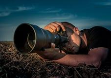 拿着在麦地的年轻摄影师照相机在温暖的日落 免版税图库摄影
