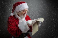 拿着在黑暗的背景的愉快的圣诞老人葡萄酒纸 免版税库存图片