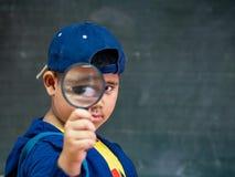 拿着在黑板前面的男孩放大镜 bac 免版税库存照片