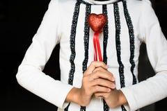 拿着在黑背景的女孩红色心脏 免版税库存图片