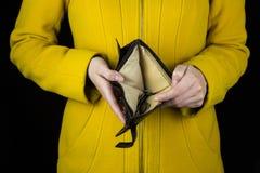 拿着在黑背景,特写镜头的女孩一个空的钱包 图库摄影