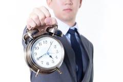 拿着在令人不快的面孔表示的商人一个时钟-企业和时间概念 免版税库存照片