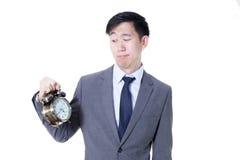 拿着在令人不快的面孔表示的年轻亚洲商人一个时钟-企业和时间概念 库存照片